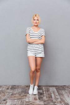 Comprimento total de uma jovem atraente em pé com os braços cruzados sobre a parede cinza