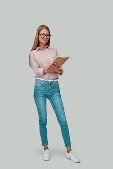 Comprimento total de uma jovem atraente escrevendo algo e sorrindo em pé contra um fundo cinza
