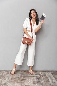 Comprimento total de uma jovem atraente, vestindo roupa de verão, em pé, isolado sobre uma parede cinza, mostrando o passaporte com as passagens aéreas