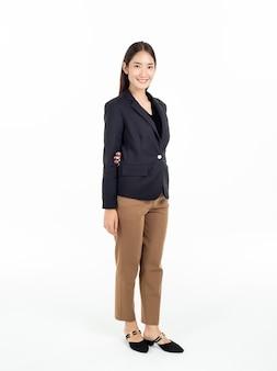 Comprimento total de uma jovem e bonita mulher de negócios asiática de terno preto e calça marrom em pé