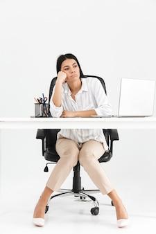 Comprimento total de uma jovem empresária atraente e entediada, sentada na mesa, isolada sobre uma parede branca