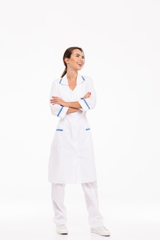 Comprimento total de uma jovem médica confiante vestindo uniforme em pé, isolado sobre uma parede branca