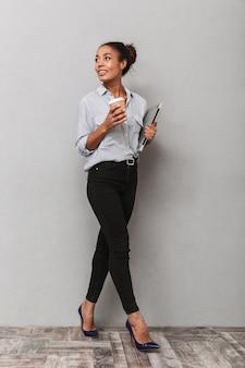 Comprimento total de uma jovem mulher de negócios na áfrica, vestindo camisa, andando isolada, segurando um laptop, bebendo café para viagem