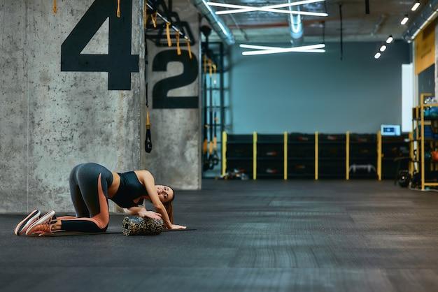Comprimento total de uma jovem mulher esportiva em roupas esportivas, se exercitando com rolo de espuma fazendo alongamento