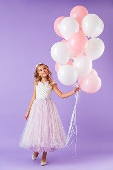 Comprimento total de uma linda garotinha vestida com vestido de princesa, de pé isolada sobre a parede violeta, segurando um monte de balões