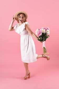 Comprimento total de uma linda jovem loira alegre com um vestido de verão em pé, isolada na parede rosa, segurando um buquê de peônias, posando