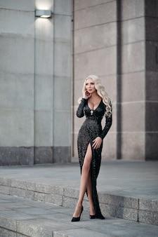 Comprimento total de uma linda mulher loira magra com cabelos longos ondulados e seios grandes posando em um vestido preto cintilante e salto alto na rua.