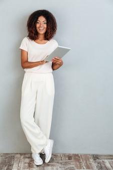 Comprimento total de uma mulher afro-americana sorridente casual em pé