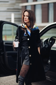 Comprimento total de uma senhora elegante em um casaco preto e botas de couro, usando um lenço colorido ao redor do pescoço. ela está carregando uma xícara de café para viagem contra um carro aberto na rua.