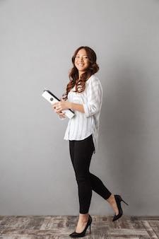 Comprimento total de uma sorridente mulher de negócios asiática em pé