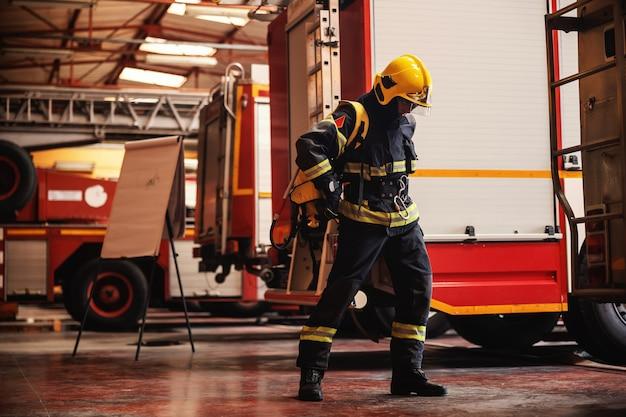 Comprimento total do bravo bombeiro em pé no corpo de bombeiros em uniforme de proteção completo e se preparando para a ação.