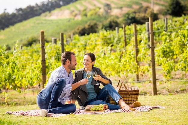 Comprimento total do casal brindando o copo de vinho na vinha