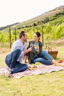 Comprimento total do casal sorridente, brindando o copo de vinho