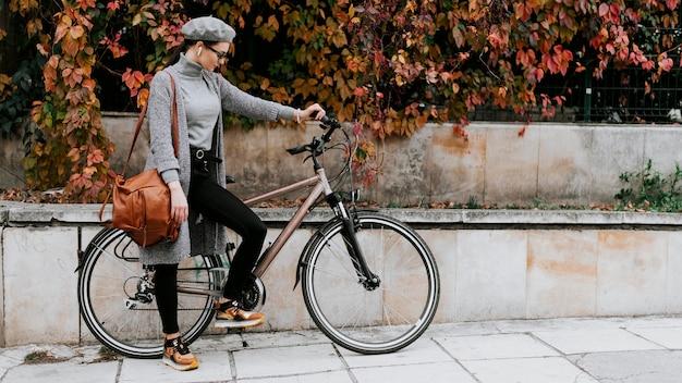 Comprimento total do corpo de mulher e bicicleta