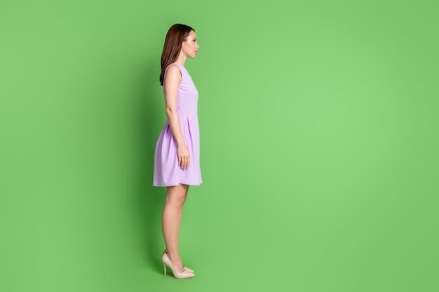 Comprimento total do corpo, tamanho do corpo, perfil lateral, dela ela é bonita, atraente, bonita, adorável, na moda, em pé, posando em linha reta, posando de fundo de cor verde