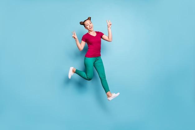Comprimento total do corpo virou foto de alegre positiva fofa linda linda namorada encantadora mostrando duplo sinal v enquanto corria e pulava isolado em calças calças cor pastel parede azul