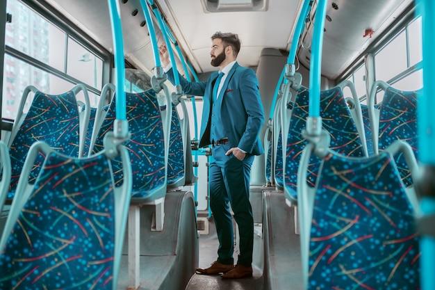 Comprimento total do empresário caucasiano pensativo em terno azul em pé no transporte público e indo para o trabalho.