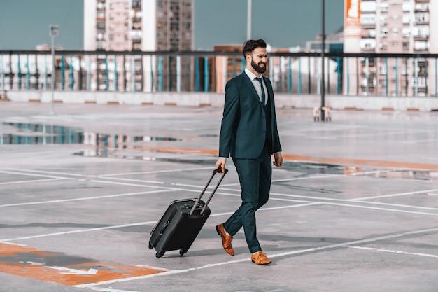 Comprimento total do empresário sorridente com roupa formal com bagagem andando no estacionamento. conceito de viagem de negócios.