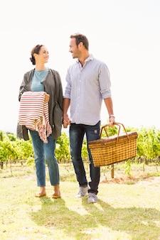 Comprimento total do homem com a mulher segurando a cesta no gramado