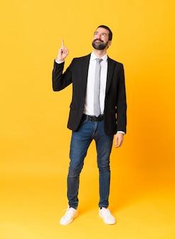 Comprimento total do homem de negócios sobre parede amarela isolada, apontando para cima e surpreso