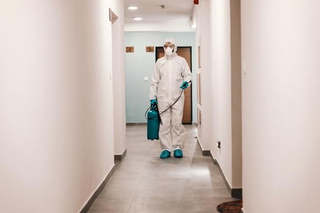 Comprimento total do homem em um terno estéril, desinfetando o corredor do edifício. proteção do conceito de corona.