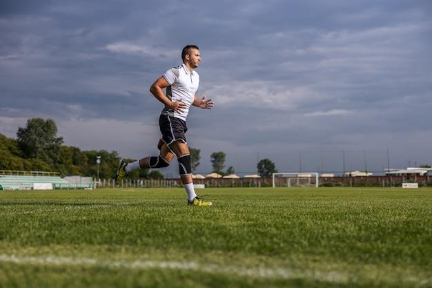 Comprimento total do jogador de futebol em forma correndo no campo.