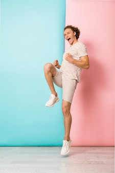 Comprimento total do jovem animado pulando e comemorando