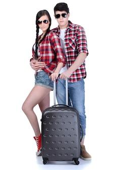 Comprimento total do jovem casal andando com malas de viagem.