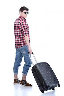 Comprimento total do jovem turista masculino em pé com a mala.