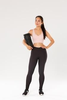 Comprimento total do sorridente treinador de ginástica feminina asiática confiante e motivado, garota fitness em roupas esportivas, olhando ao redor satisfeito, segurando o rolo de espuma para usar após o treino, em pé com o equipamento de treinamento.