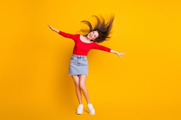 Comprimento total do tamanho do corpo dela ela agradável atraente adorável alegre alegre despreocupada fina esbelta garota dançando se divertindo desfrute do bom humor isolado brilhante brilho vívido vibrante fundo de cor amarela