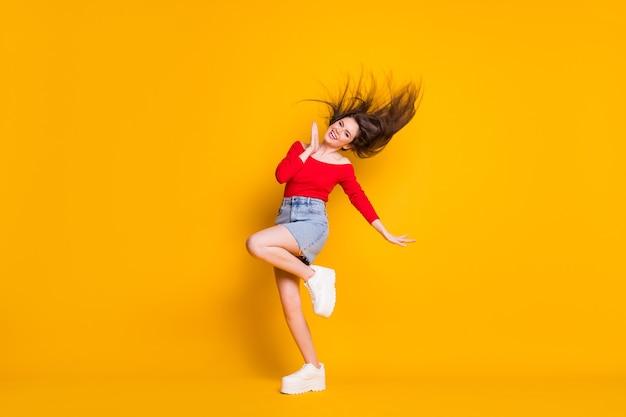 Comprimento total do tamanho do corpo dela ela é agradável atraente adorável alegre alegre fino ajuste feminino esbelta garota dançando se divertindo no verão isolado brilhante brilho vívido fundo de cor amarela vibrante