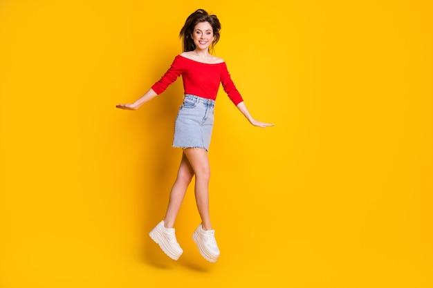 Comprimento total do tamanho do corpo dela ela é agradável, atraente, adorável, alegre, alegre, magra, magra, pulando, se divertindo, caminhando, desfrute, isolado, brilhante, vívido, brilho, vibrante, cor amarela, fundo