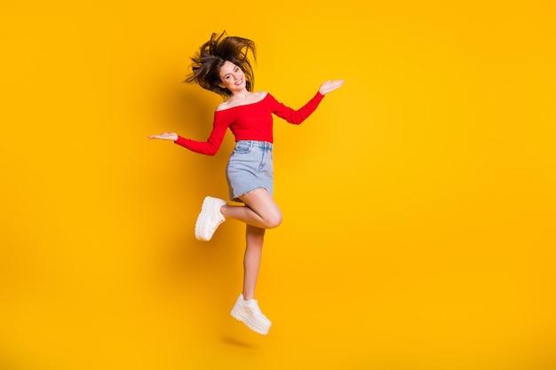 Comprimento total do tamanho do corpo dela ela é agradável, atraente, charmosa, alegre, alegre, magra, pulando, se divertindo, passando o fim de semana isolado brilhante brilho vívido fundo de cor amarela vibrante