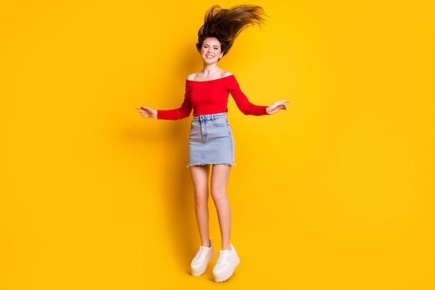 Comprimento total do tamanho do corpo dela ela é legal atraente adorável muito charmoso alegre alegre menina magra magra pulando se divertindo brincando isolado brilhante brilho vívido fundo de cor amarela vibrante