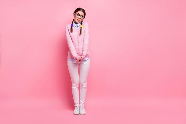 Comprimento total do tamanho do corpo dela ela é legal, atraente, fofa, tímida, modesta, garota de cabelos castanhos, geek, mordendo os lábios, decidindo dilema questão estudo isolado sobre fundo rosa pastel