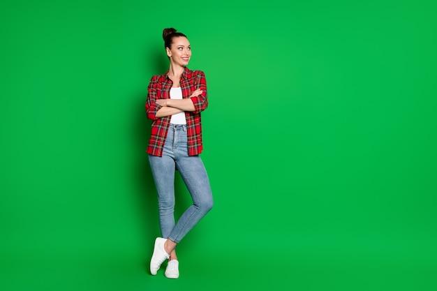 Comprimento total do tamanho do corpo dela ela é legal atraente muito adorável conteúdo alegre alegre garota de cabelos castanhos vestindo uma camisa xadrez posando isolada em um fundo de cor verde vibrante de brilho vívido brilhante