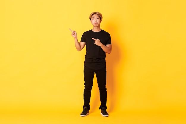 Comprimento total do triste cara coreano bonito com cabelo loiro fazendo uma careta de chateação, apontando os dedos no canto superior esquerdo, mostrando o logotipo com pesar, parede amarela de pé.