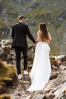 Comprimento total e vista traseira de um jovem casal de noivos caminhando pelas montanhas de mãos dadas.