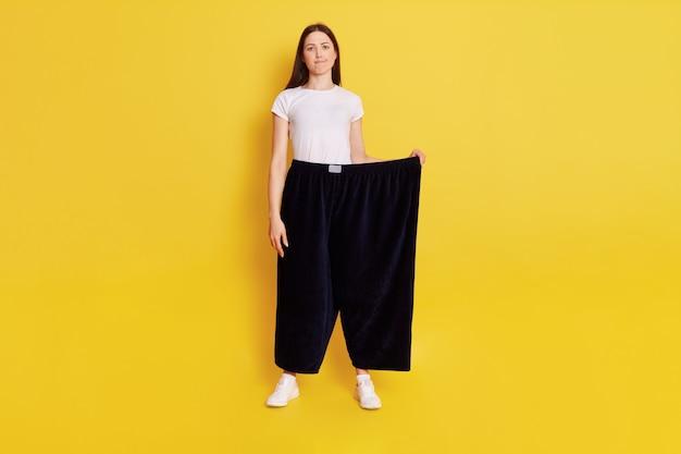 Comprimento total jovem adulta caucasiana, vestindo camiseta casual e calça tamanho muito grande, olha para a câmera com expressão perplexa e perplexidade, franze os lábios, isolado sobre a parede amarela.