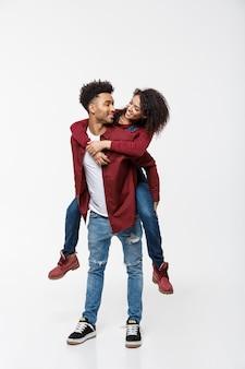 Comprimento total jovem atraente americano africano senhora cavalgando nas costas do namorado dela.