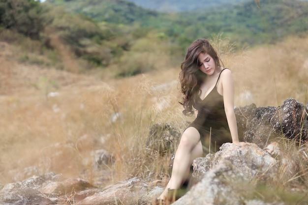 Comprimento total jovem mulher asiática de vestido preto, sentado na natureza ao ar livre