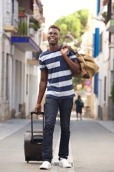 Comprimento total jovem viajante masculino andando na rua com mala