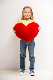 Comprimento total. menina bonitinha segurando coração vermelho grande.