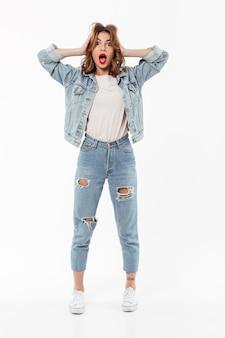 Comprimento total mulher chocada em roupas jeans, segurando sua cabeça sobre a parede branca