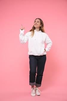 Comprimento total mulher loira sorridente usando roupas casuais apontando e olhando para cima enquanto posava com o braço no quadril sobre a parede rosa