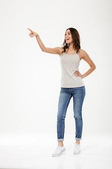 Comprimento total mulher morena feliz com o braço no quadril, apontando e olhando para longe sobre cinza