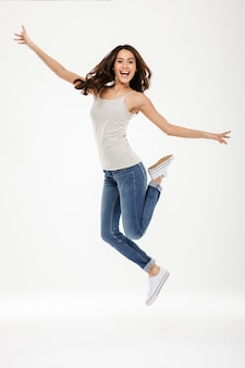 Comprimento total mulher morena feliz pulando e se alegra enquanto olha para a câmera sobre cinza
