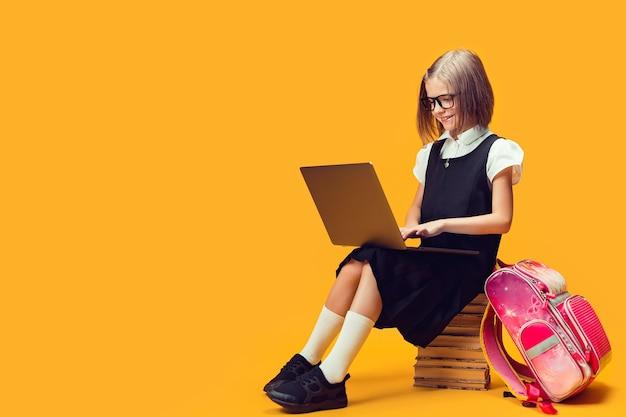 Comprimento total sorridente colegial sentada na pilha de livros, trabalhando no laptop, crianças, conceito de educação