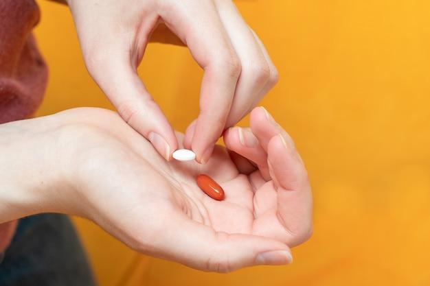 Comprimido branco e cápsulas em uma mão feminina em laranja